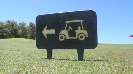Golf iron is picked up walking by a golf buggy sign.