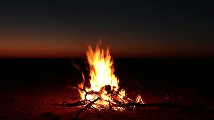 Outdoor wood campfire burning brightly against sunset