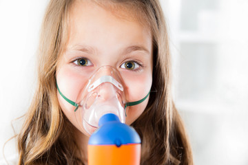Little girl using an inhaler indoors