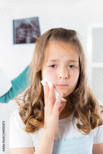 Girl with toothache,doctor holding and looking at x-ray of teeth