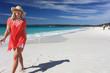 Happy smiling woman walking along beautiful sandy beach