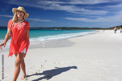 Happy smiling woman walking along beautiful sandy beach