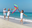 Happy young family with flying a kite