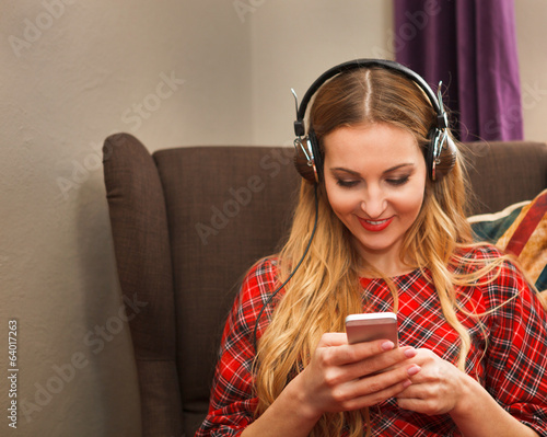 Portrait of happy young woman with mobile phone listening to the