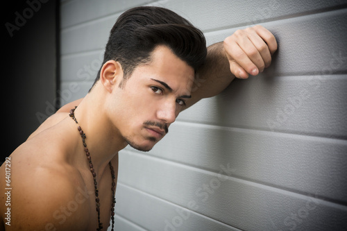 Young man shirtless leaning against wall with one arm