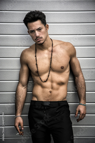 Athletic shirtless young man with moustache and necklace