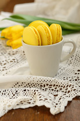 Cup with yellow macaroon and yellow tulips on vintage lace doily