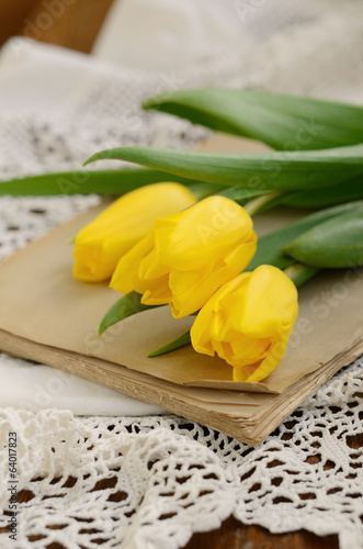 Yellow tulips upon old book