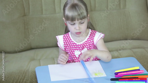 Little girl is drawing with colored felt pens