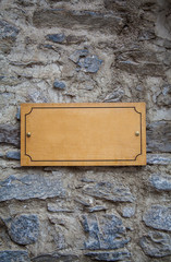 Wooden Signboard on the Stone Wall