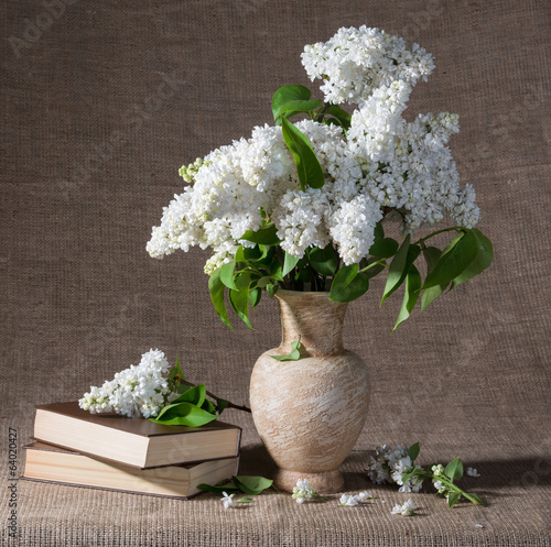 Blooming branches of lilac in vase and books