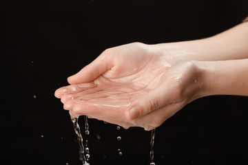 Human hands with water splashing on them on black background