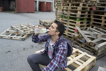 Young man sitting & drinking water on a wooden pallet
