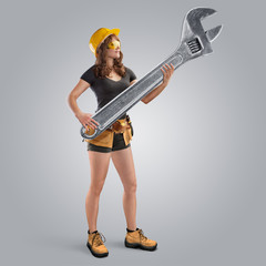 worker girl in a helmet holding a wrench