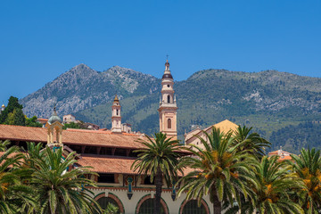 Belfry among houses and palms in Menton, France.