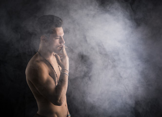 Shirtless young man smoking cigarette with a lot of smoke around