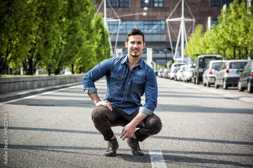 Attractive smiling man sitting in the middle of city road