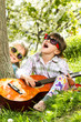 Two little girls have a fun and playing a guitar outdoor