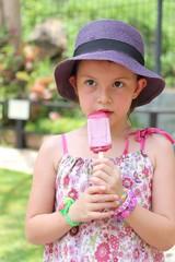 Girl eating ice-cream in zoo wearing rainbow loom