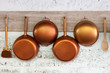 Copper  kitchen utensil on the white painted brick wall - 64024421