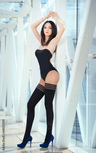 Sensual elegant woman wearing a black body posing indoor