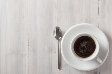 Cup of coffee from above on white wooden table