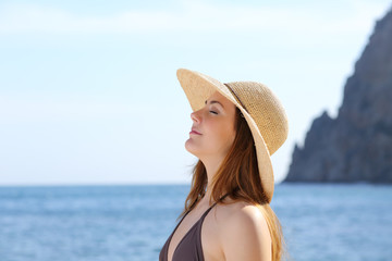 Happy woman breathing fresh air on the beach with a hat