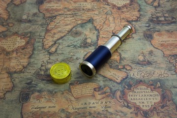 Bitcoins and a vintage telescope on an antique map