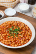 chickpeas stewed in tomato sauce on a plate, vertical