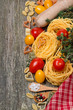 pasta, tomatoes and spices on wooden background, top view