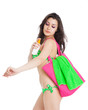 brunette girl wearing green swimsuit holding bottle of sunscreen