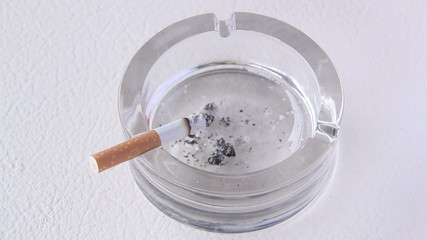 A cigarette butt being put into in a glass ashtray.