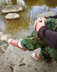 man sitting near water