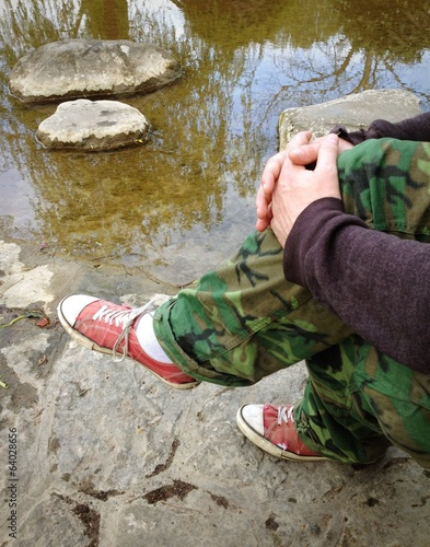man sitting near water