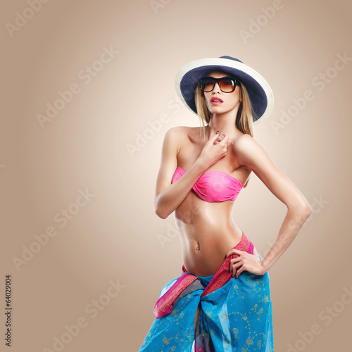 Sexy pose of a woman in hat wearing a pink bikini