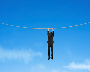 Businessman holding rope and hanging in sky