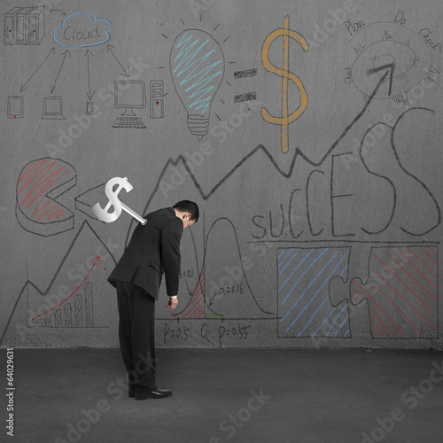 Man tired with winder and business doodles on wall