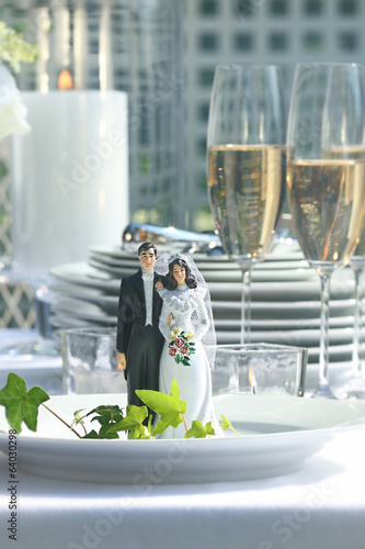 Close-up of figurine couple on dinner plate at reception