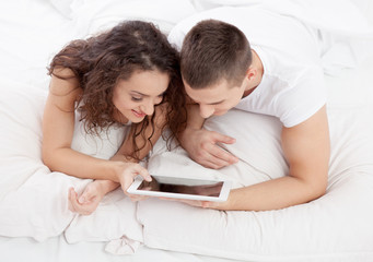 Young couple lying on the bed using tablet pc