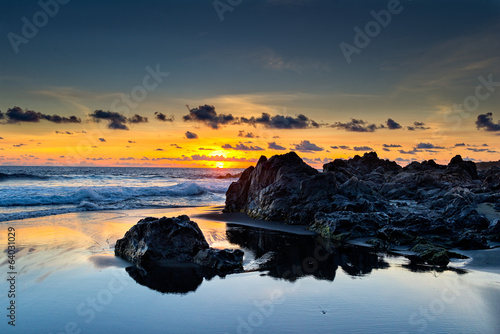 Wild beach and lava rocks at sunset