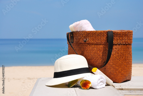 hat, bag, sun glasses and towel on a tropical beach