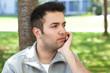 Nachdenklicher junger Mann mit grauer Weste im Park