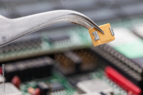 Pick yellow capacitor with pliers