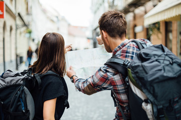 Couple of backpackers looking at city map
