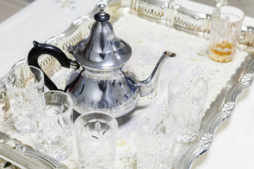 Moroccan tea theme. Metal teapot with glasses