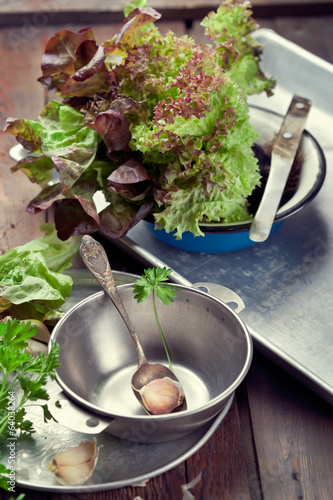 Old metal bowl and kitchen utensils with lettuce and parsley