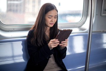 Young Asian woman using tablet pc riding train