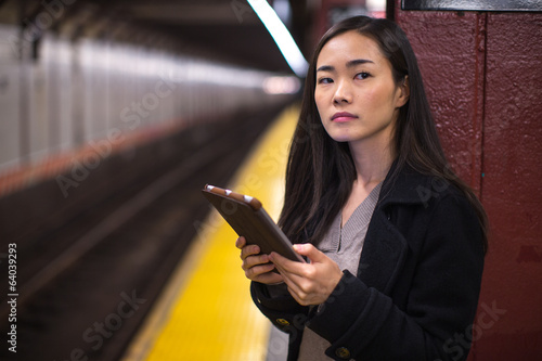 Young Asian woman using tablet pc subway platform