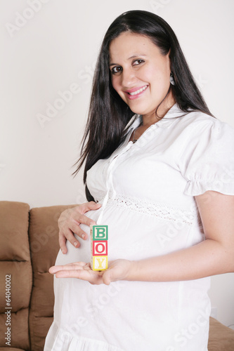 Beautiful hispanic pregnant woman having the word boy with woode