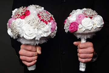 Man holds two wedding bouquet for bride